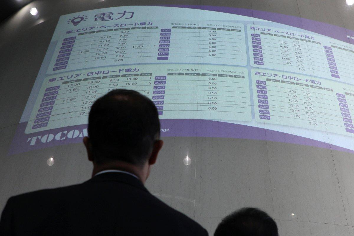 電力先物の取引が開始され、初値がついた相場表を見つめる市場関係者ら=2019年9月17日、東京都中央区