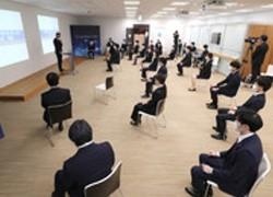 入社式であいさつするコニカミノルタの山名昌衛社長(左上)。新型コロナウイルス感染防止のため、新入社員の間隔をあけて行われた=1日午前、東京都千代田区