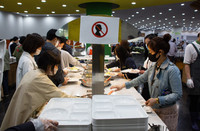 マスクや手袋を着用した利用客で混み合うソウルのカフェテリア=20日(EPA時事)