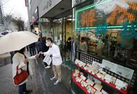 新型コロナウイルスの影響で存続が困難となり、最後の営業日を迎えた歌舞伎座前の弁当店「木挽町辨松」。152年の老舗の廃業を惜しむ人で開店前から大勢の人が訪れ、店は整理券を配って対応した=4月20日、東京都中央区