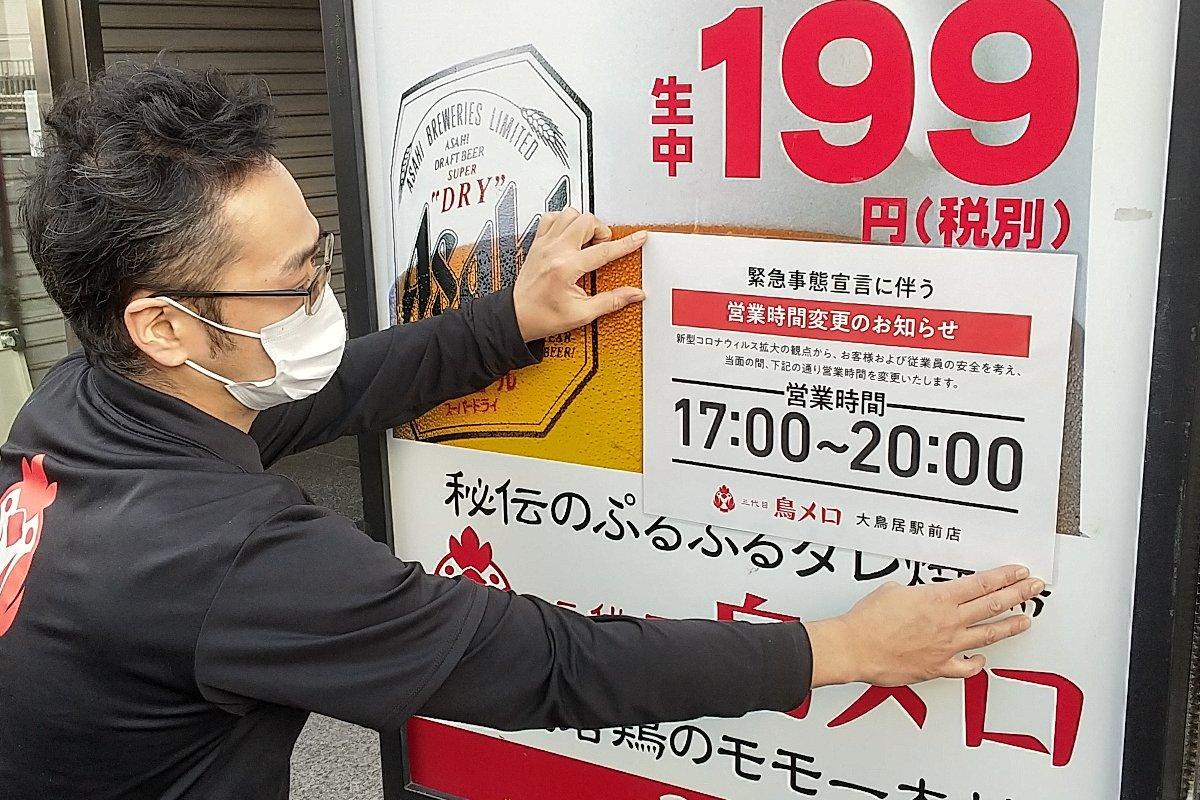 営業時間変更の案内を貼り出す居酒屋の店長=1月8日午後、東京都大田区